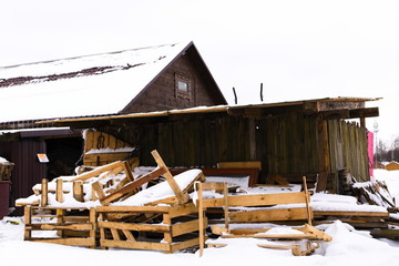 Barn boards near a wooden house in the village in the winter