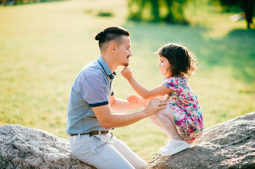 Dad and daughter summer outdoor activity. Loving father playing with his cheerful baby. Parent and child have fun in park. Little girl lsitting on stone with father. Happy family lifestyle portrait.