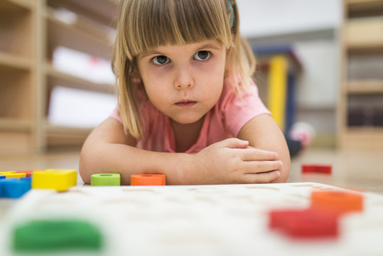 Little girl is angry while playing with alphabet blosc puzzl