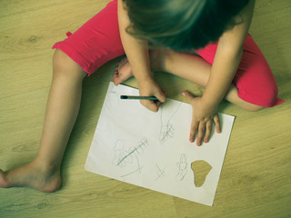 a small child draws a child's drawing on paper
