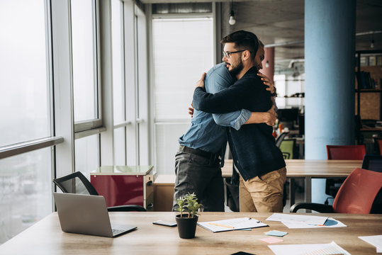 Two business colleagues hug and congratulate each other with success in their office