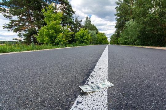Dollar bills on asphalt road