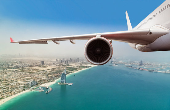 Commercial jet plane flying above Dubai city.