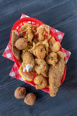 seafood basket with fried shrimp, fish, and hush puppies flat lay