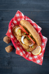 seafood basket with fried shrimp on sandwich with tomato and onion flat lay