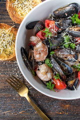 Cooked seafood mussels with shrimp, tomatoes, and herbs in bowl