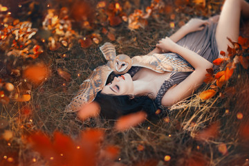 bright autumn art photo, goddess rests in autumn orange forest under protection of cute little owl, girl with dark hair in spirit of nature, sexy hot lady, sleeping beauty in glare of sun and fire