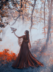 mysterious lady in gorgeous burgundy red luxurious dress and curly dark hair stands in thick foggy forest, queen of autumn with owl, witch vampire looking for victim for ceremony, sun rays in smoke
