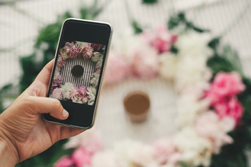 Hand holding phone and taking photo of coffee drink in beautiful pink and white peonies frame on table, flat lay. Good morning concept. Happy mothers day. Instagram blogging and workshop