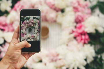 Instagram blogging and workshop. Hand holding phone and taking photo of coffee drink in beautiful pink and white peonies frame on table, flat lay. Good morning concept. Happy mothers day.