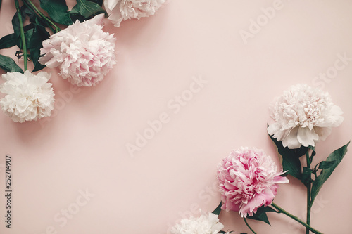 Happy mother's day. International womens day. Greeting card mockup. Stylish pink and white peonies  border on pink paper flat lay with space for text.