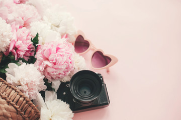 Stylish photo camera, sunglasses, straw  bag with pink and white peonies on pink paper flat lay with space for text. Hello summer.  International womens day.