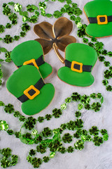 Saint Patrick's Day Green Leprechaun hat cookies with gold four leaf clover flat lay