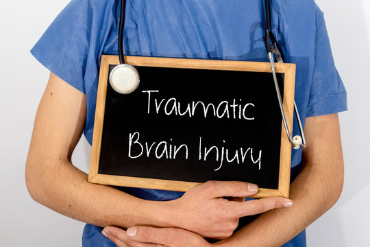 Doctor shows information on blackboard: traumatic brain injury.  Medical concept.