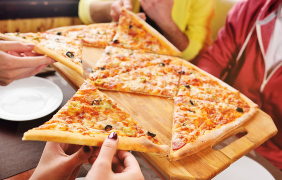a group of friends grab a fresh hot pizza sitting in a cafe. Hands with slices of pizza close-up.