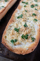 baked cut french bread with butter, garlic, and parsley