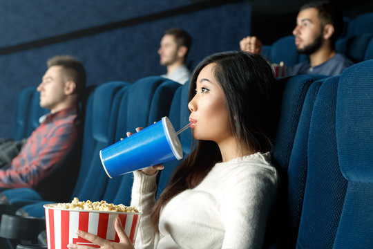 So entertained. Portrait of a young Asian woman drinking her beverage watching movie attentively at the local cinema