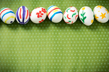 Easter eggs painted by hand on a beautiful green background in white peas. Festive background. Easter ideas. Space for text. Happy easter.