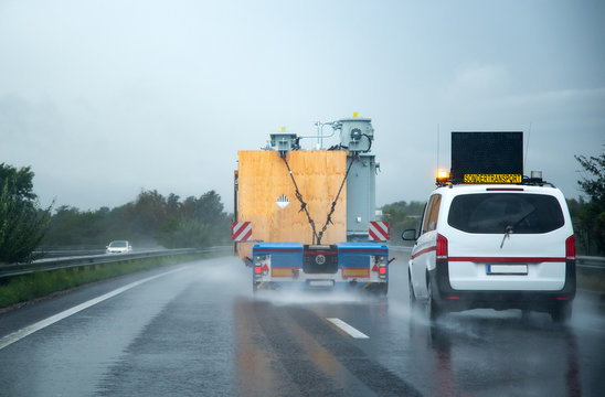 Car escorting heavy industrial truck on the road