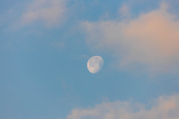 Three quarter moon against blue sky with pink clouds after sunrise
