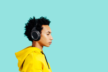 Profile portrait of a young man with headphones listening to music
