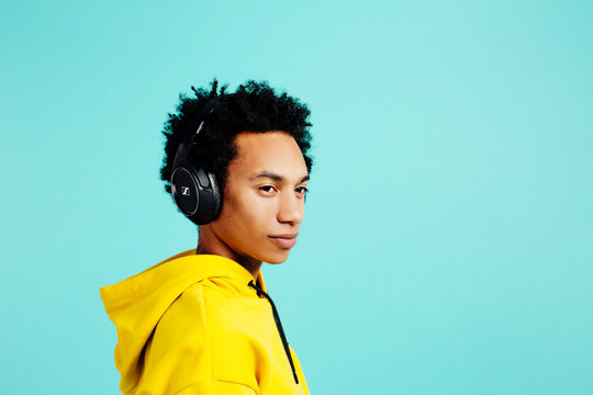 Portrait of a young man with headphones looking to the side,  isolated on blue background