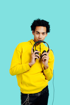 Portrait of a young man  in yellow with headphones, against a blue background