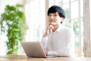young asian man using laptop in living room