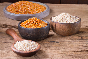 Quinoa seeds and red millet in bowl on rustic wood