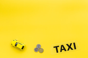 Taxi operator concept. Chip service. Sign taxi ner car toy and coins on yellow background top view copy space