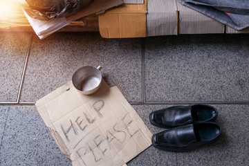 Empty space in homeless shelter on the street in modern city, someone gave shoes to homeless people, shoes for homeless people with cardboard text