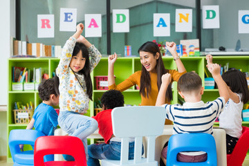 Happy Asian female teacher and mixed race kids in classroom,Kindergarten pre school concept.
