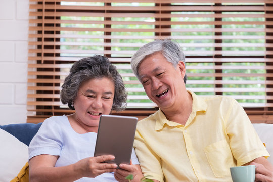 Asian senior couple learn to using table compute on sofa in living room at home.senior with technology lfiestyle.aging at home concept.