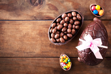 Chocolate Easter eggs on wooden background with ribbon bow and candies. Happy Easter!.