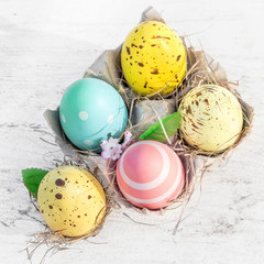 Easter eggs in egg cartoon box on white rustic wooden background close up. Festive decorations. Happy Easter!.