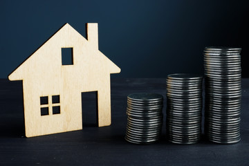 Property investment and value of home concept. Coins and model of house.