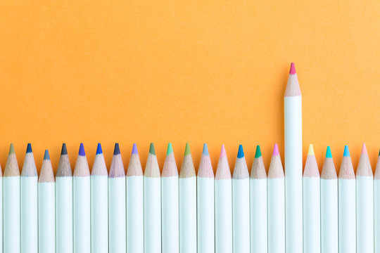 Color pencil in row with stand out pink one using as individual creativity, leadership or feminine and woman leader idea