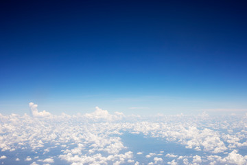 Blue sky background and white clouds soft focus, top view take a picture on airplane.