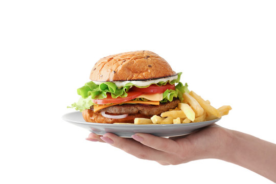 Female hand holding plate with tasty burger and french fries on white background