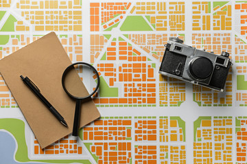 Photo camera, notebook and magnifier on city map. Travel concept