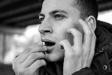 Black and white photo of male suicider taking pills outdoors, closeup
