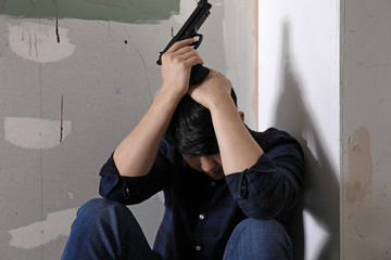 Young man with gun going to commit suicide at home