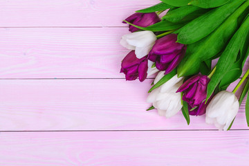 Bouquet of tulip flowers on pink wood background with copy space
