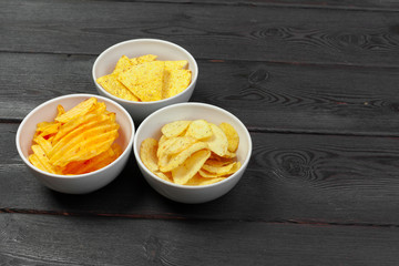 Bowls with tasty crispy potato chips