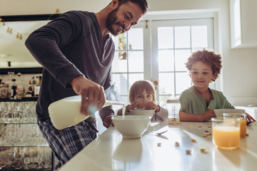 Father preparing breakfast for his kids