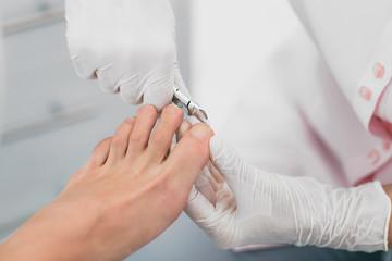 Foto auf Acrylglas Pediküre Beautician trimming clients Toenail. Hygienic Manicure Process