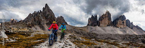 Wall mural Cycling woman and man riding on bikes in Dolomites mountains andscape. Couple cycling MTB enduro trail track. Outdoor sport activity.