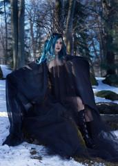 Black queen. Blue hair woman portrait in forest.