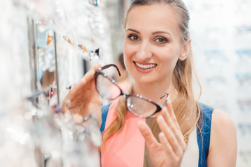 562beda887 Woman and man buying glasses at optician store getting advice from ...