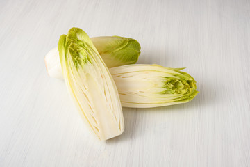 Fresh Endive or Chicory (Cichorium endivia) whole and halved on a white wooden table, copy space